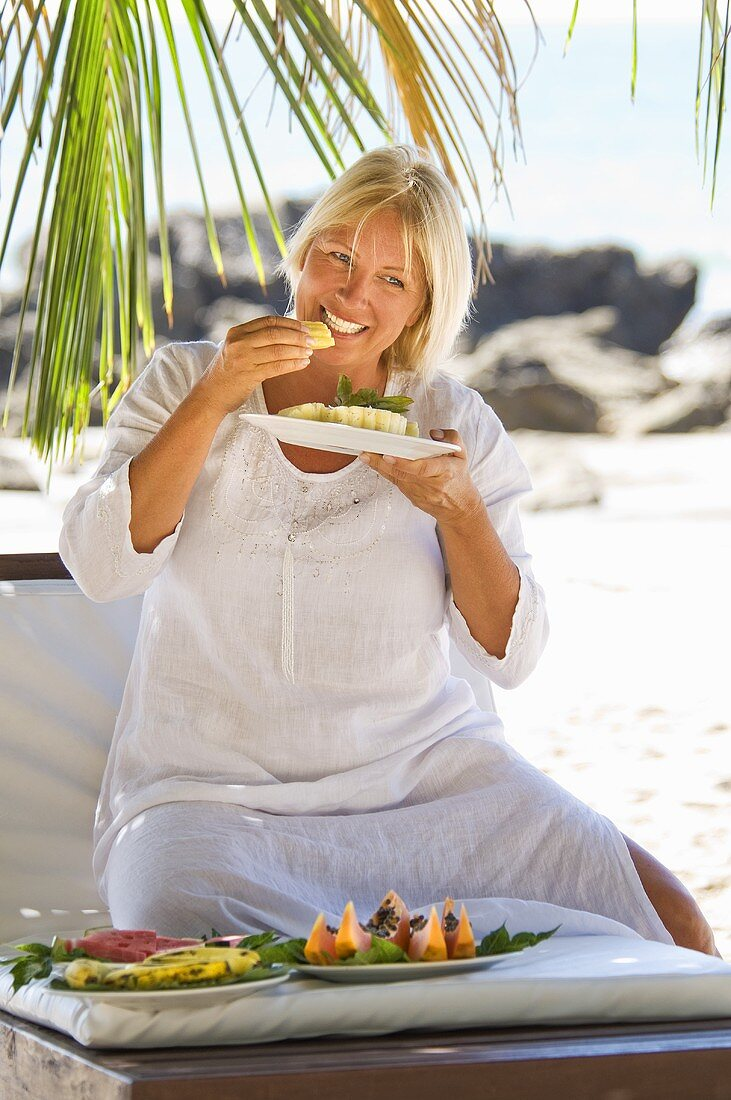 Blond woman eating pineapple on the beach