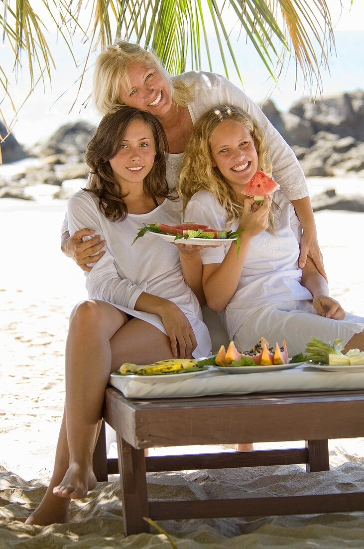 Mother and daughters eating watermelon on the beach