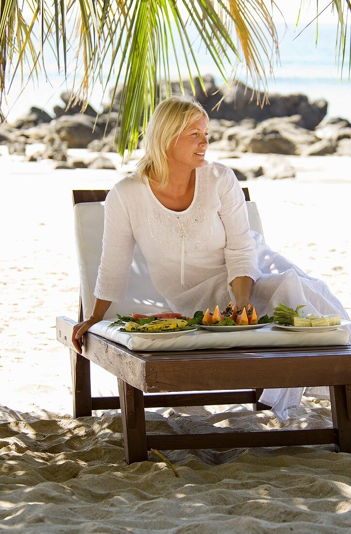 Blond woman with a plate of fruit on the beach