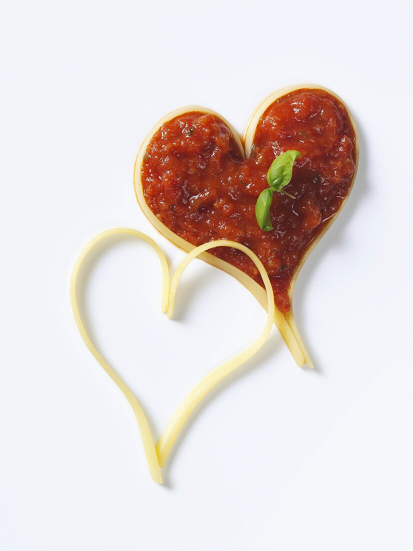 Spaghetti forming two hearts, one filled with tomato sauce