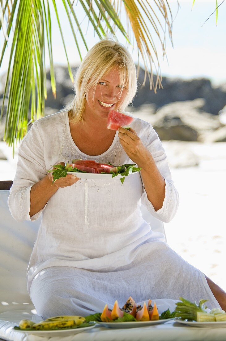 Blond woman eating watermelon on the beach