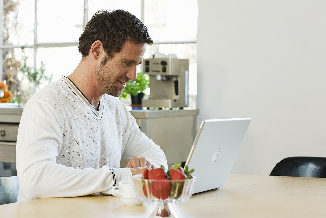 Man using laptop on kitchen table