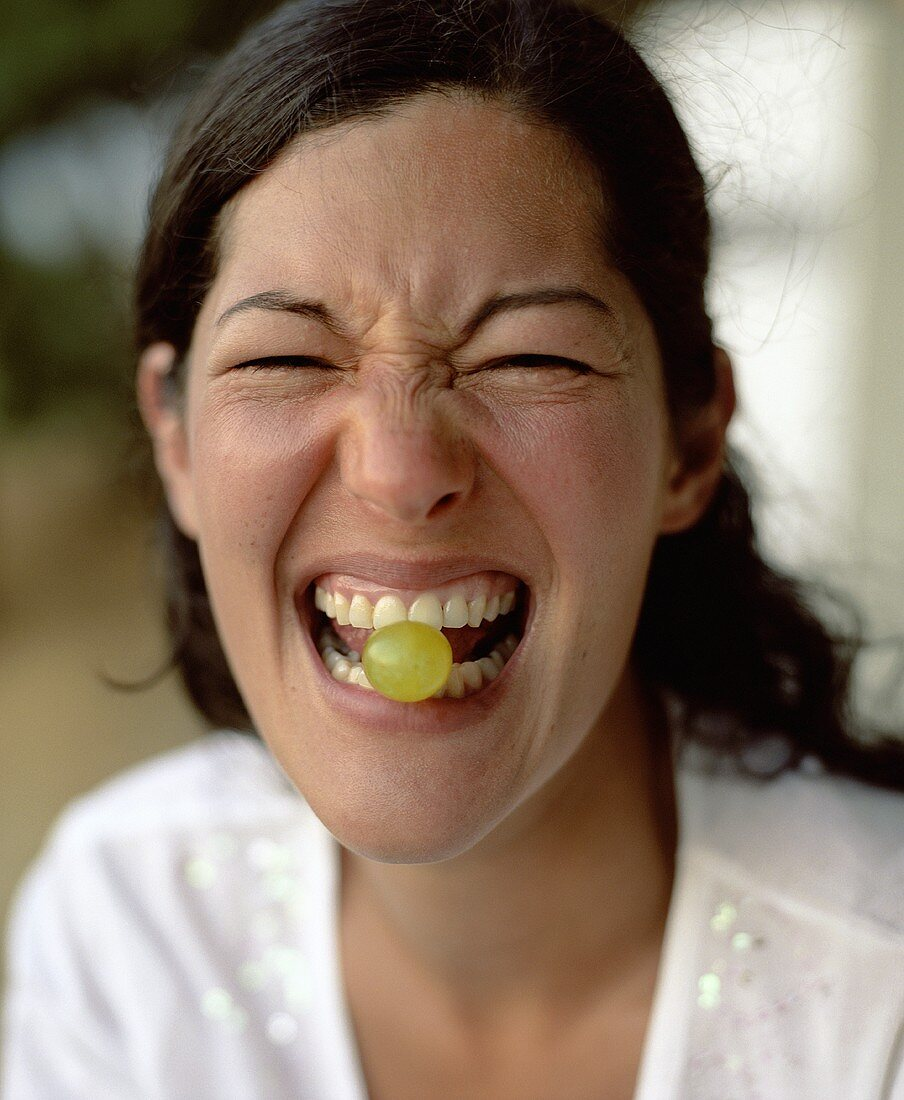Young woman with a grape between her teeth