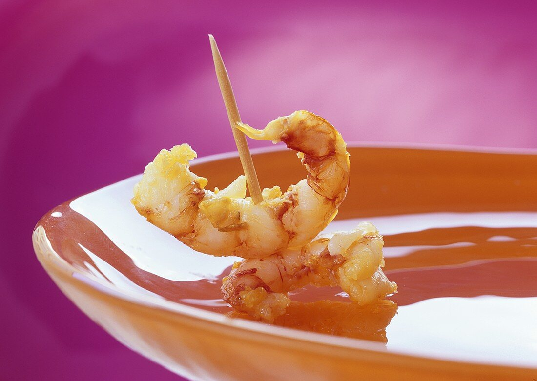 Appetiser: prawns on cocktail stick on a plate