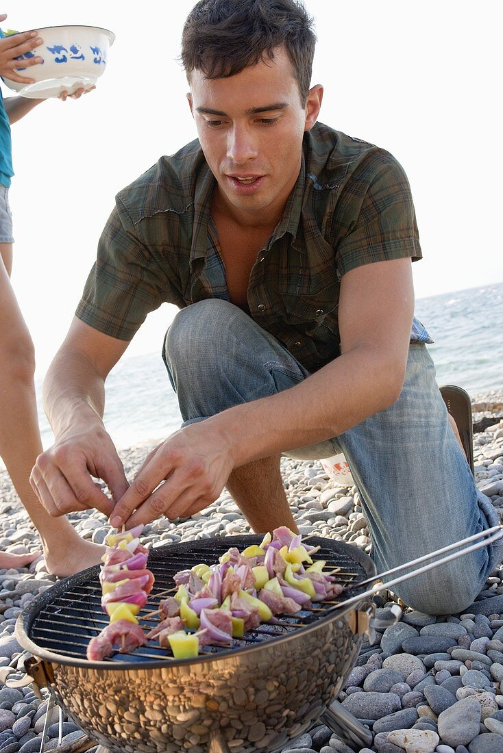 Young man placing shashlik on barbecue on beach