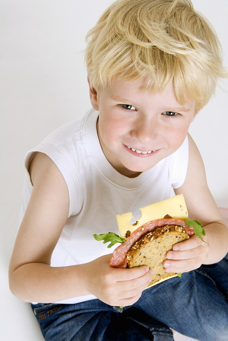 Blond boy with salami and cheese sandwich