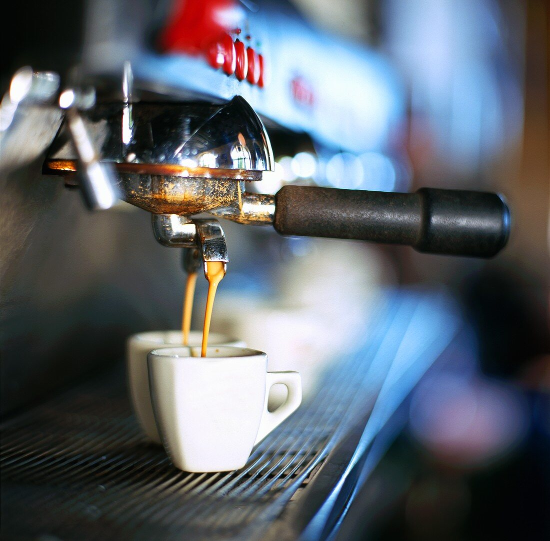 Espresso running out of machine into two cups