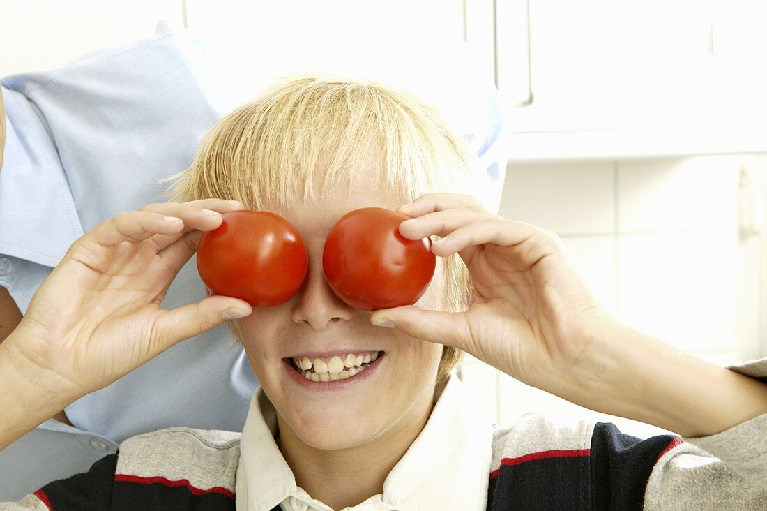 Blond boy holding two tomatoes in front of his eyes