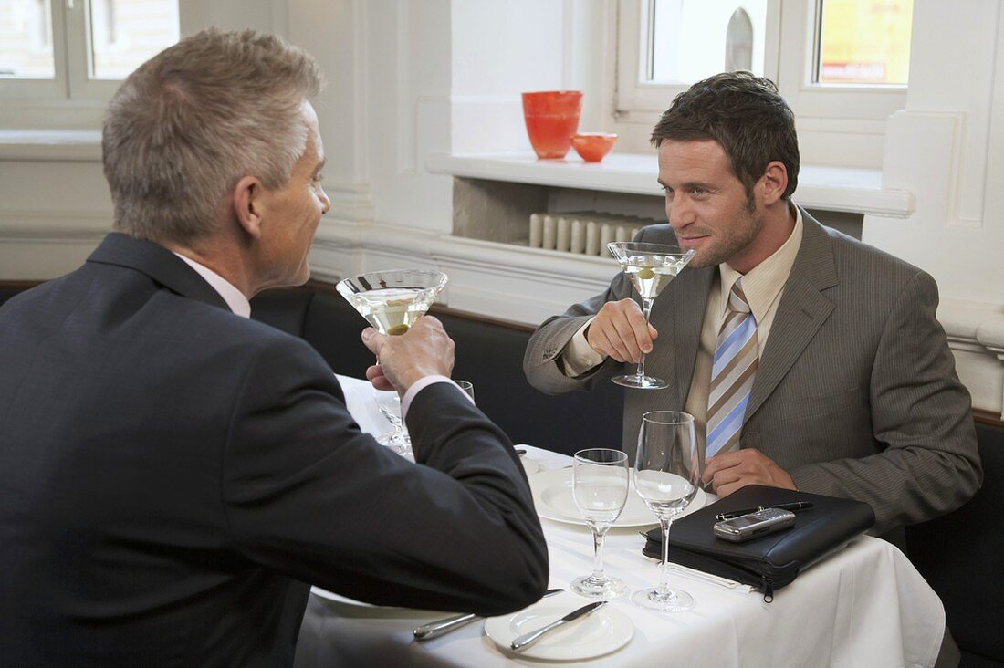 Two men drinking Martinis at a meeting in a restaurant