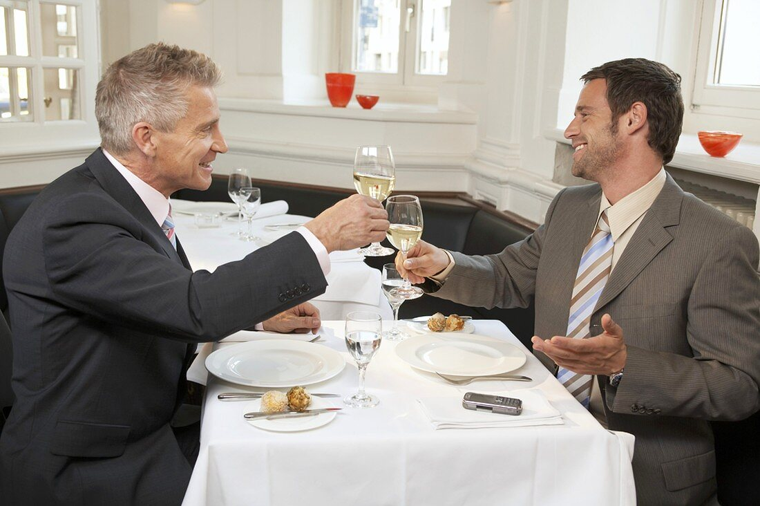 Two men drinking a glass of white wine together