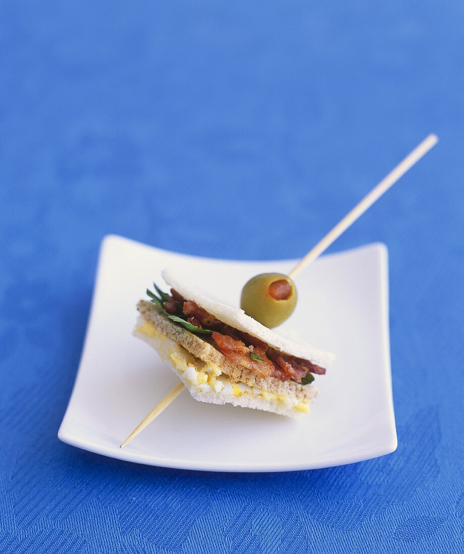 Small egg and bacon sandwich with olive on wooden cocktail stick