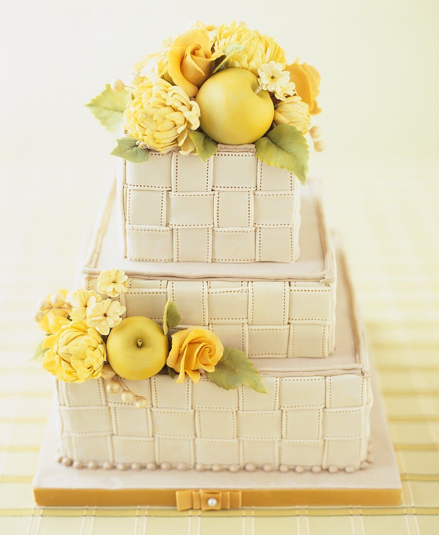 Three-tiered cake with basket-weave effect, flowers and apples