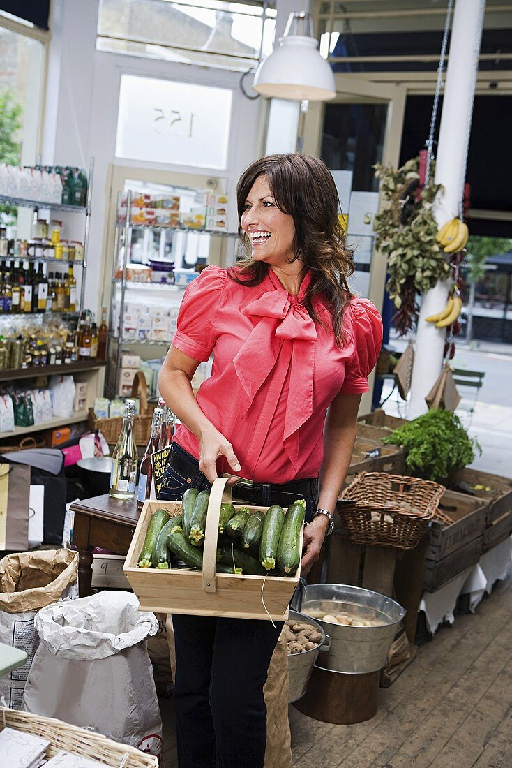 A woman in a store with a basket of courgettes