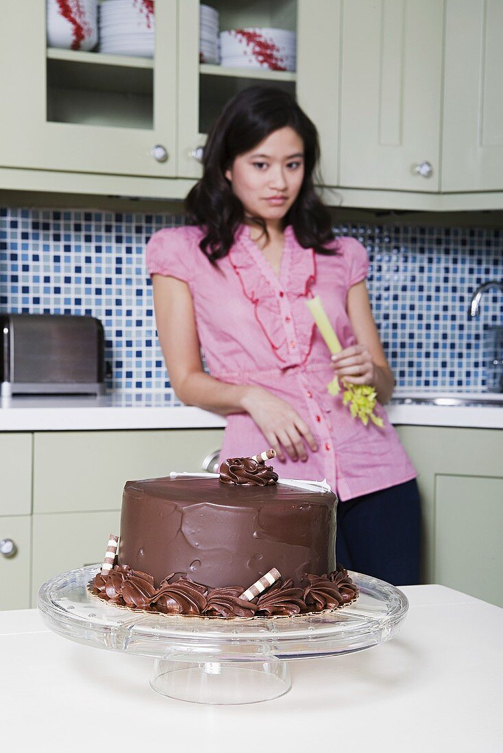 A young woman eating celery, looking at a chocolate cake