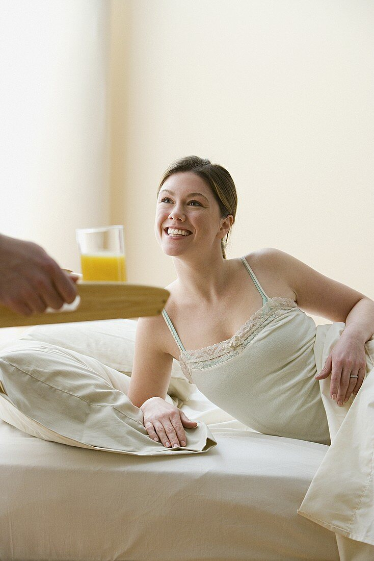 A woman being brought breakfast in bed