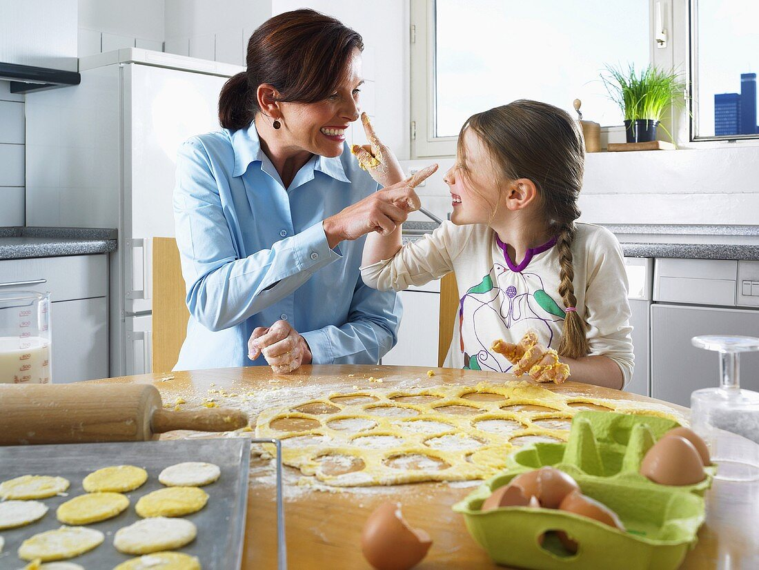 A mother and daughter messing around whilst baking