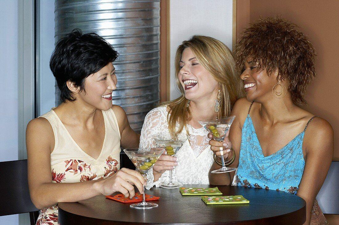 Three friends having cocktails