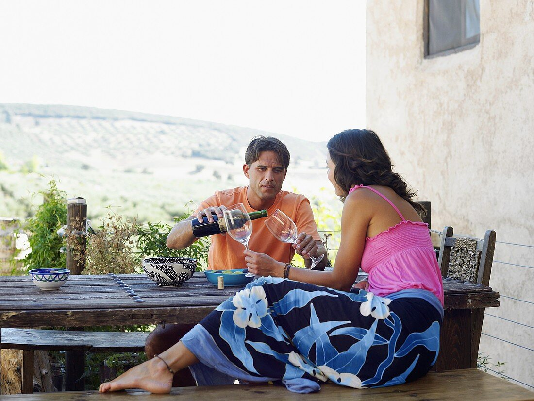 A couple sitting at a table on a terrace having wine