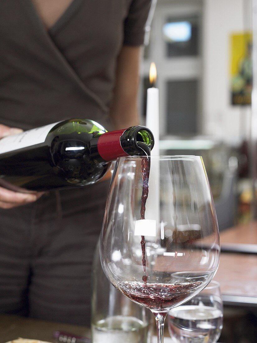 A glass of red wine being poured