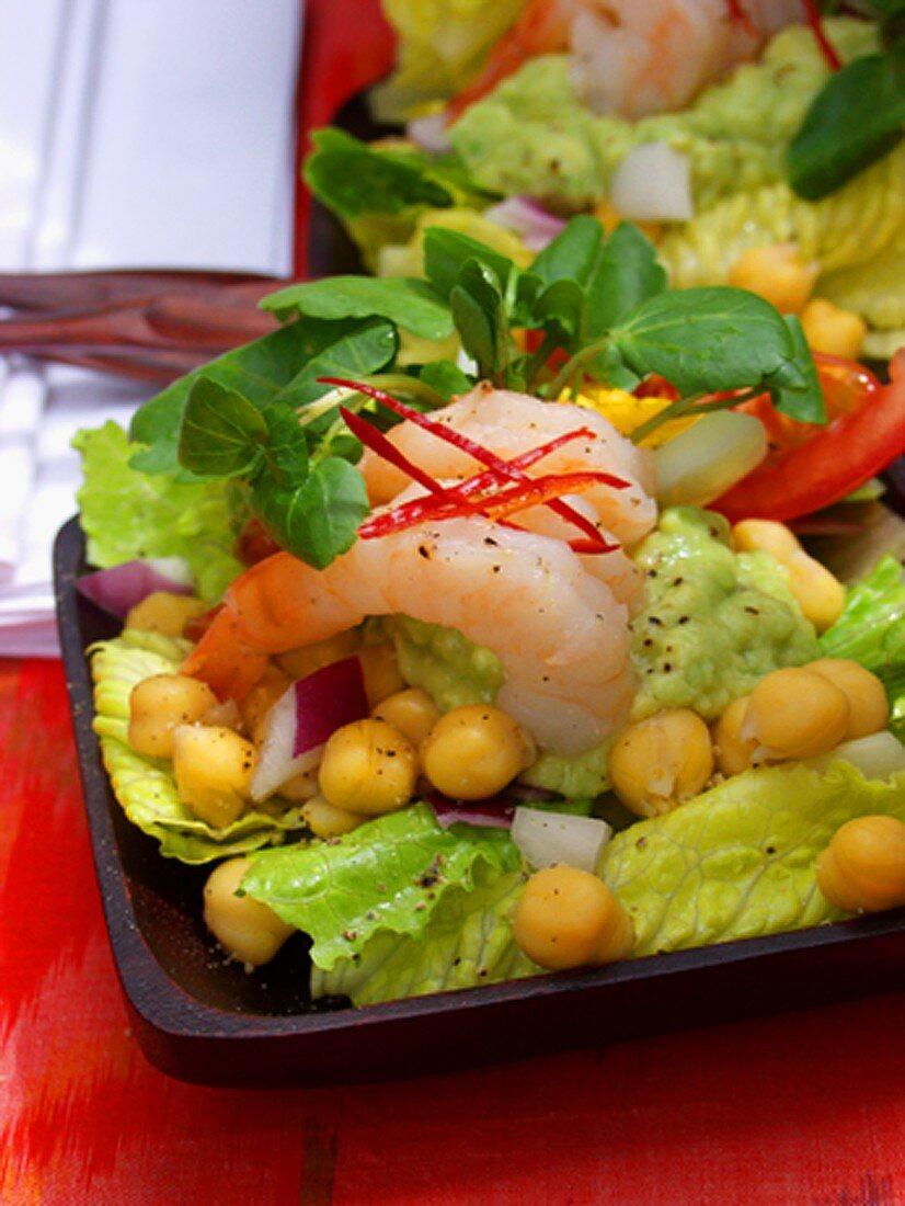 Avocado puree, shrimps & chick-peas on salad leaves