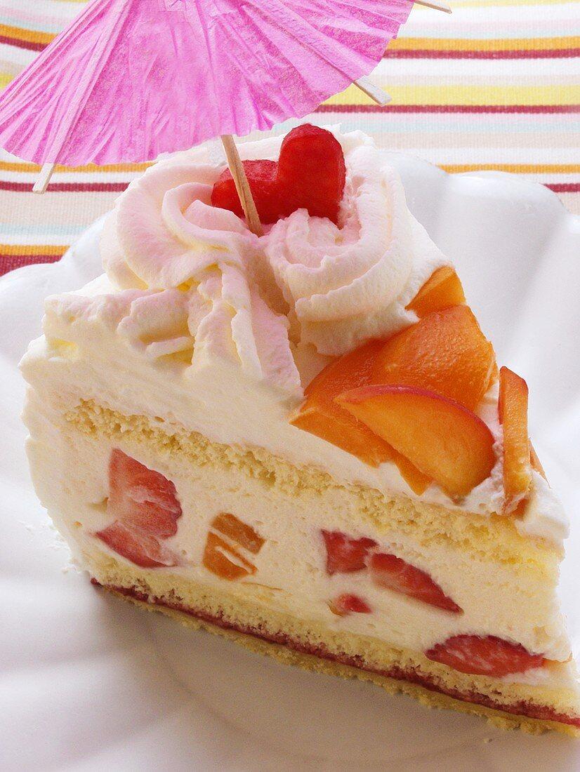 A piece of summery fruit gateau with cream; parasol