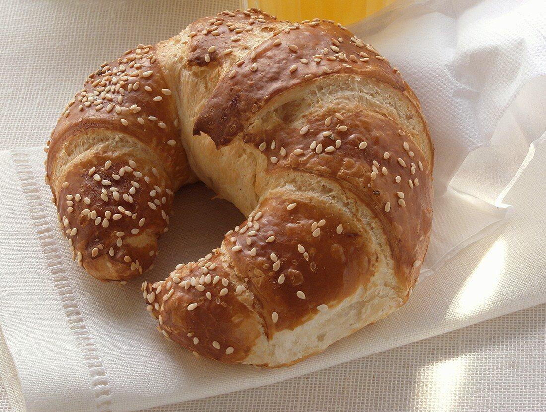 Croissant with sesame on white napkin