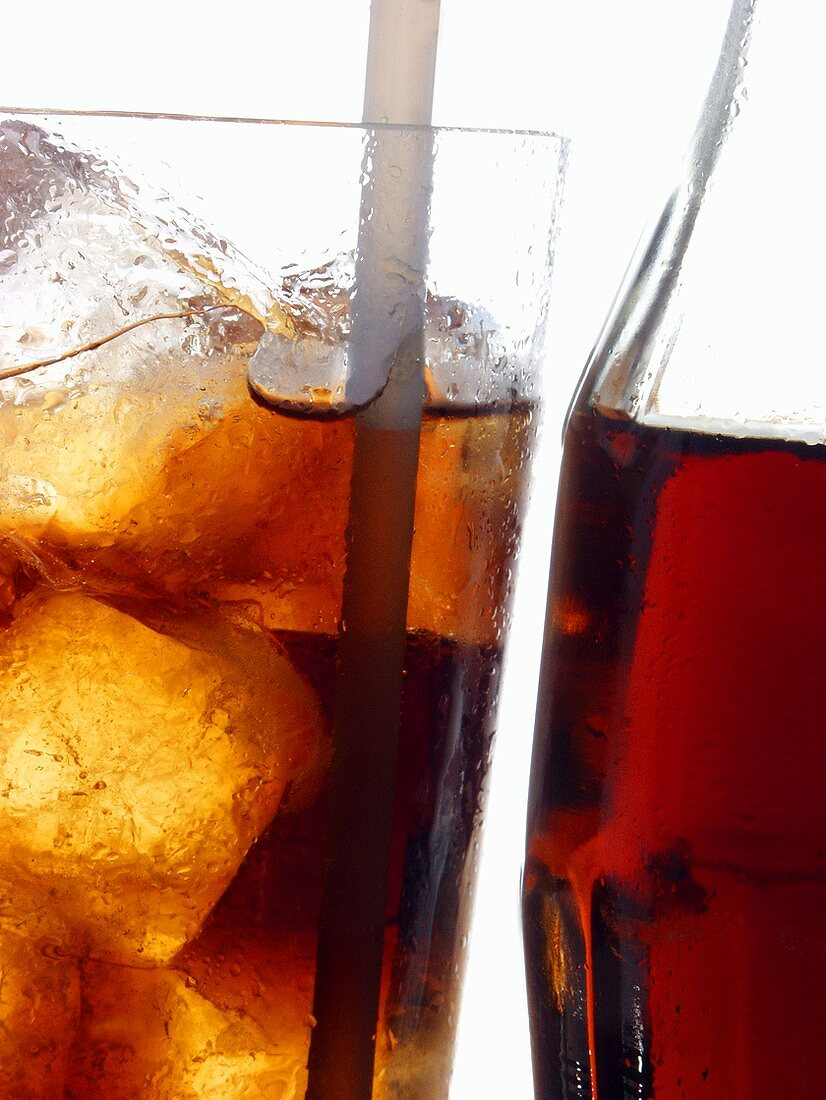Cola in bottle and glass with ice cubes and straw