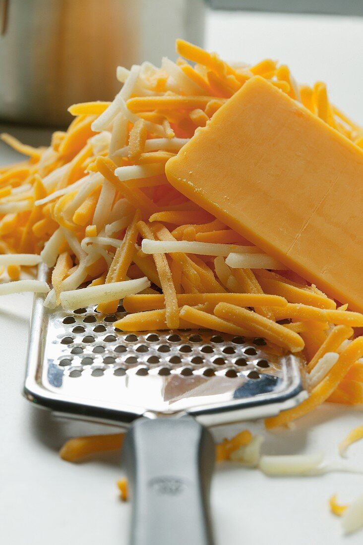 Mozzarella and Cheddar, partly grated, with cheese grater
