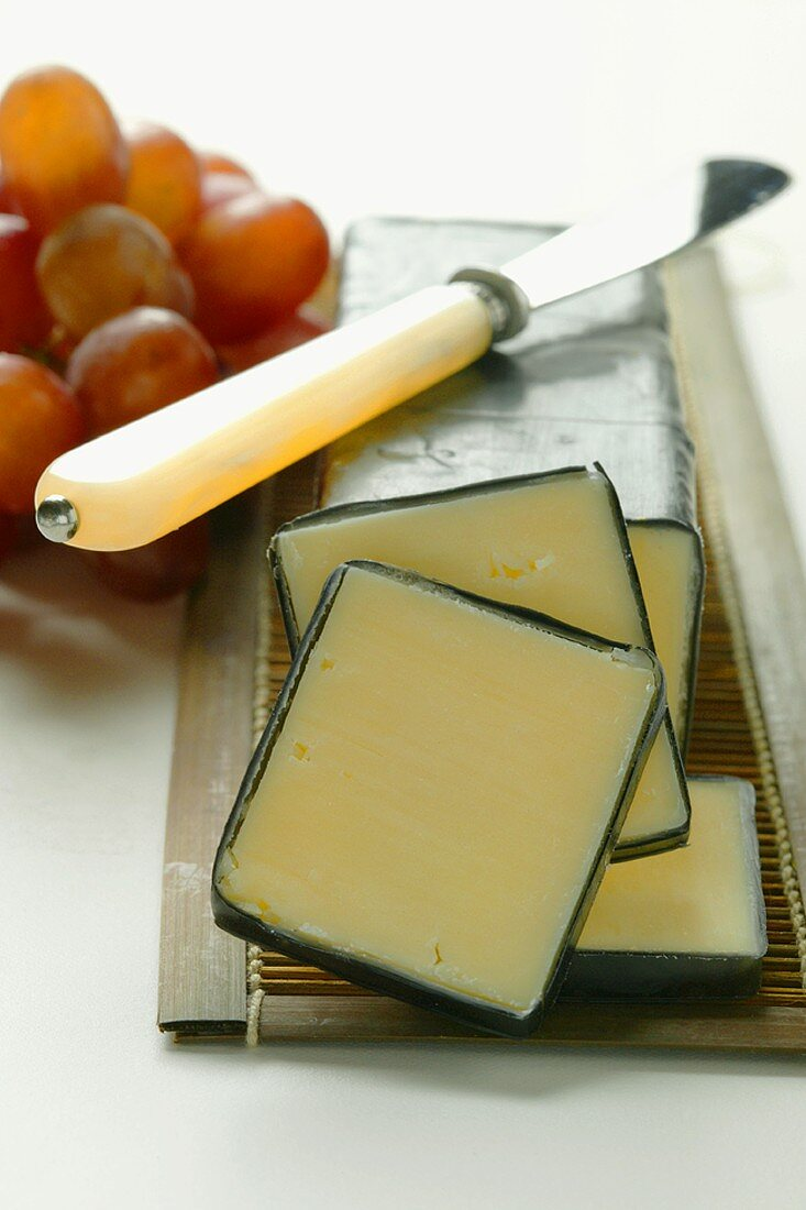 Vermont Cheddar with cheese knife and grapes