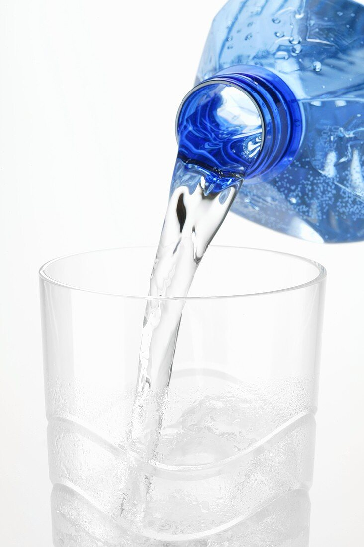 Pouring water out of plastic bottle into glass
