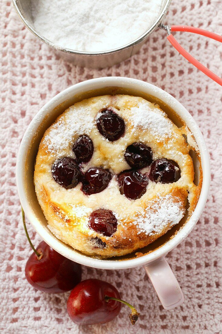 Quark and semolina pudding with cherries and icing sugar in cup
