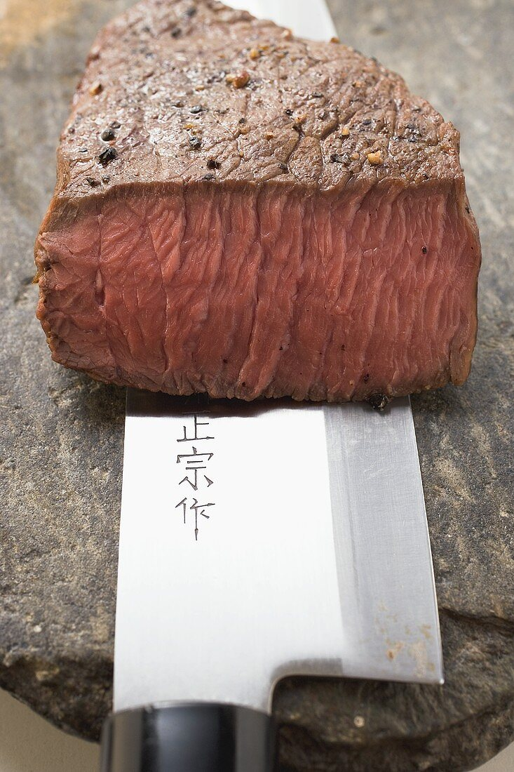 Beef steak with a piece cut off, on Asian knife