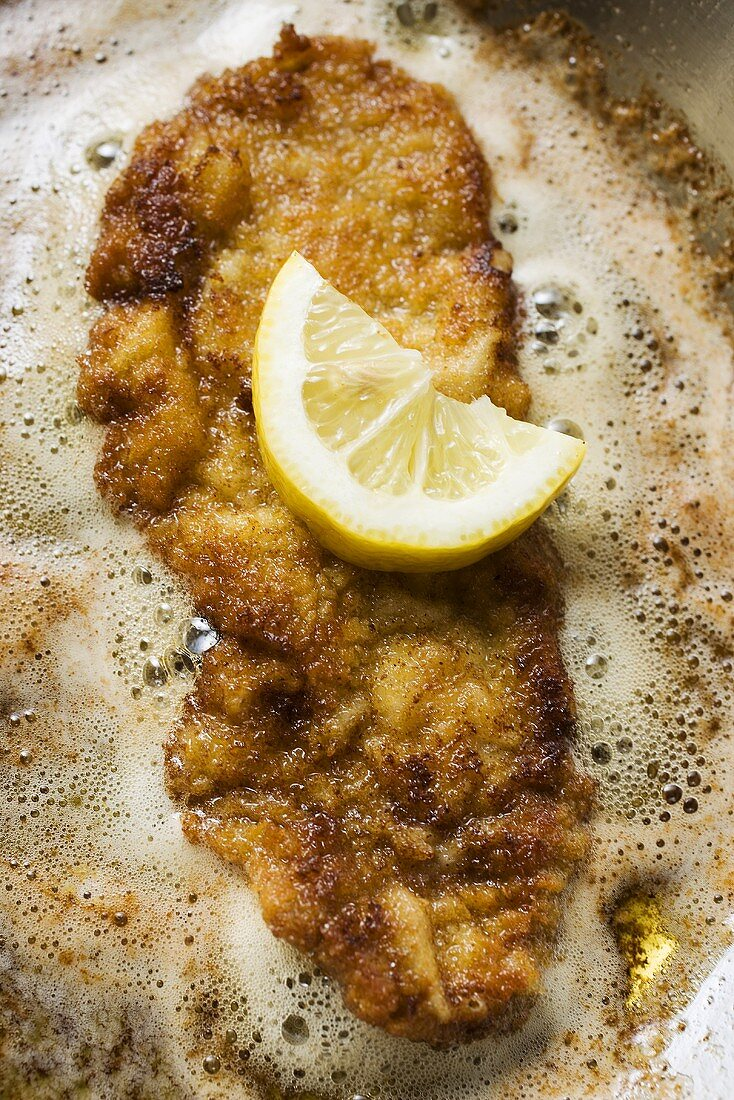 Frying escalope with lemon in frying pan