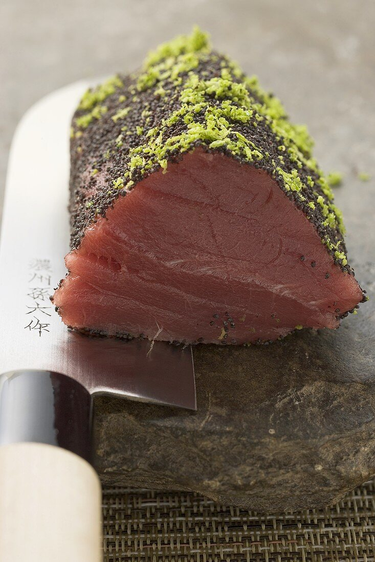 Raw tuna fillet with poppy seeds and lime zest on knife