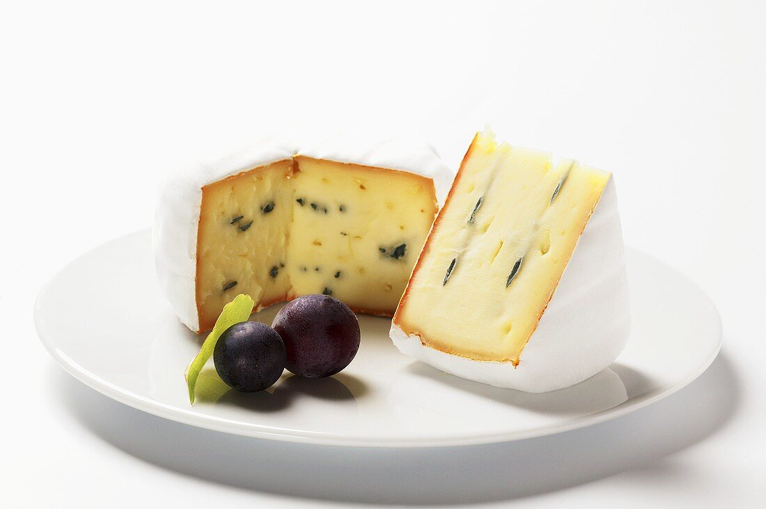 Blue cheese (Bavaria blue) with red grapes on plate