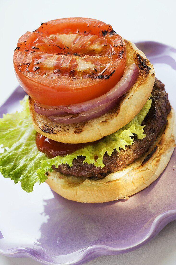 Home-made hamburger with onions and grilled tomato