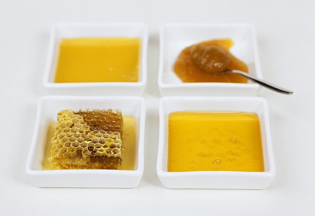 Four bowls of different types of honey