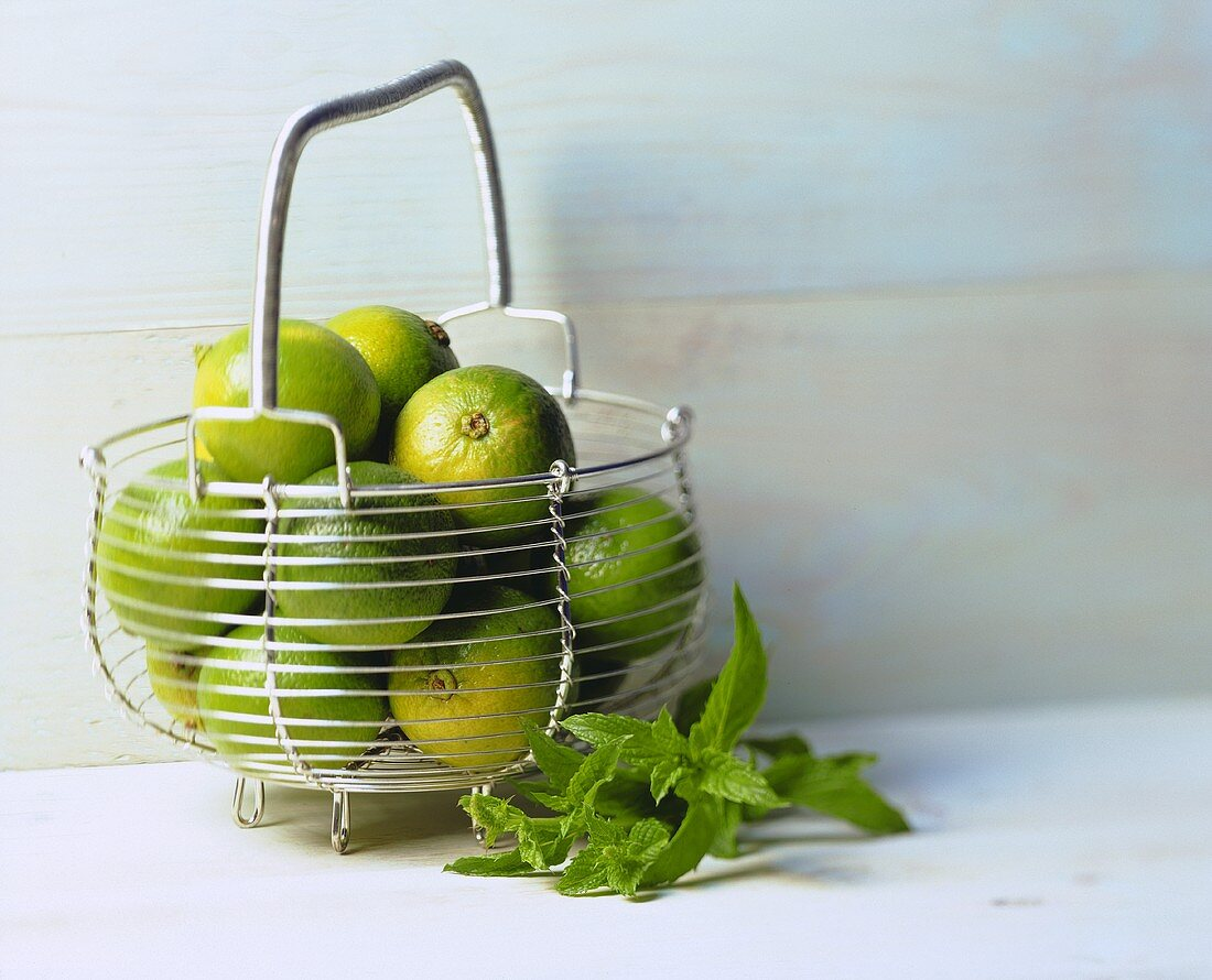 Several limes in wire basket with peppermint