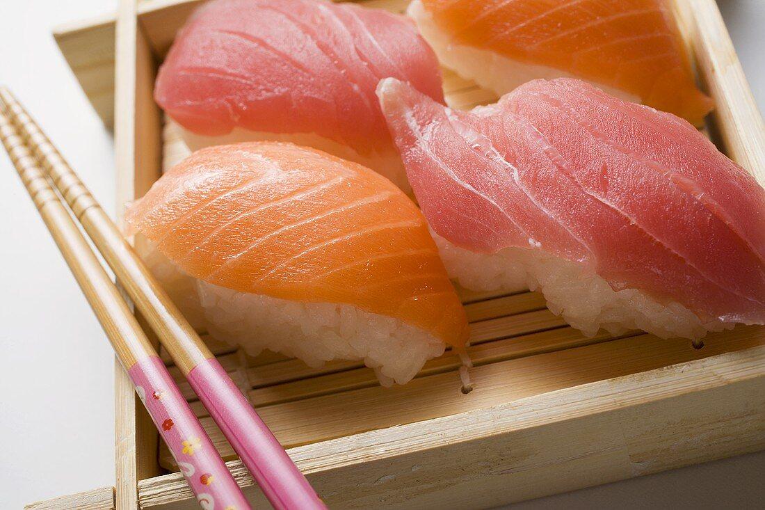 Nigiri sushi with chopsticks on bamboo mat