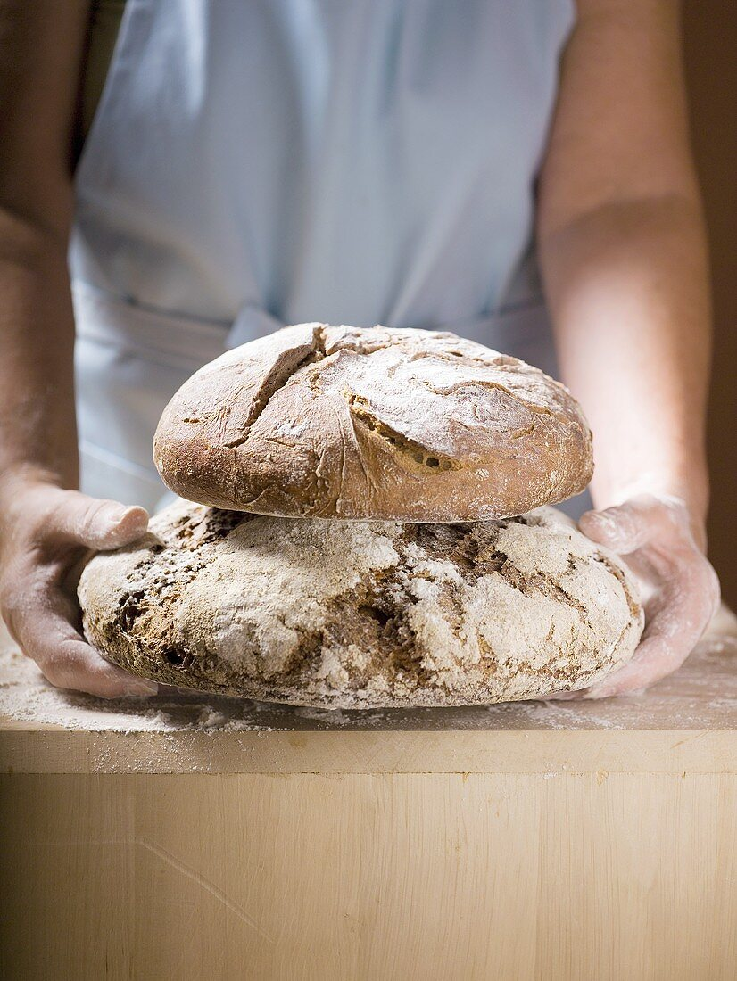 Woman holding two loaves of Bauernbrot (German farmhouse bread)
