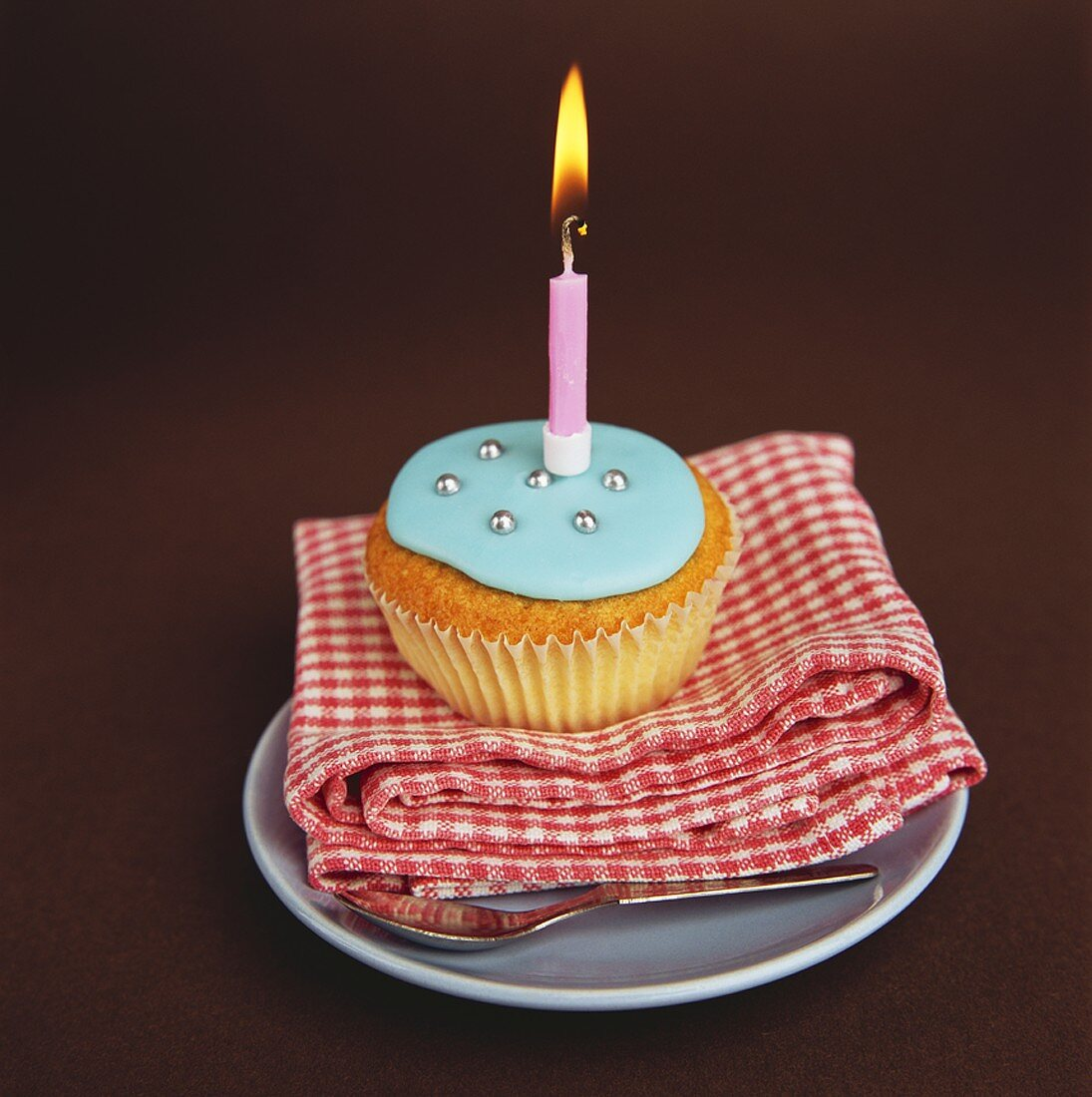 Cupcake with blue icing and a candle