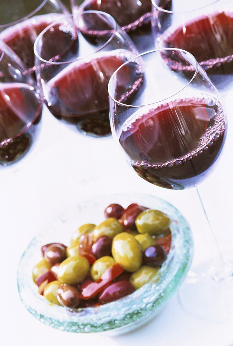 Glasses of red wine and a small dish of olives