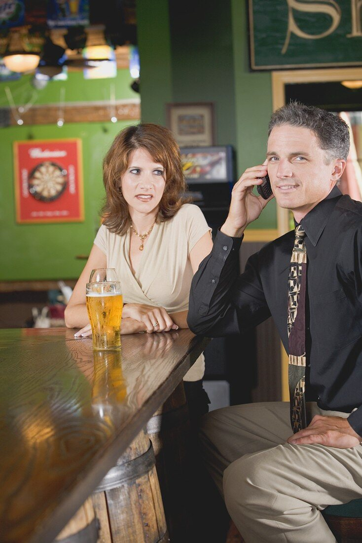 Woman standing disapprovingly beside man on phone in a pub