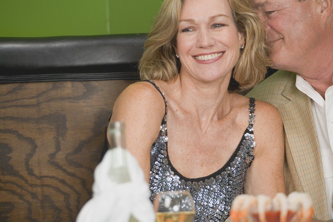 Mature man embracing woman in restaurant