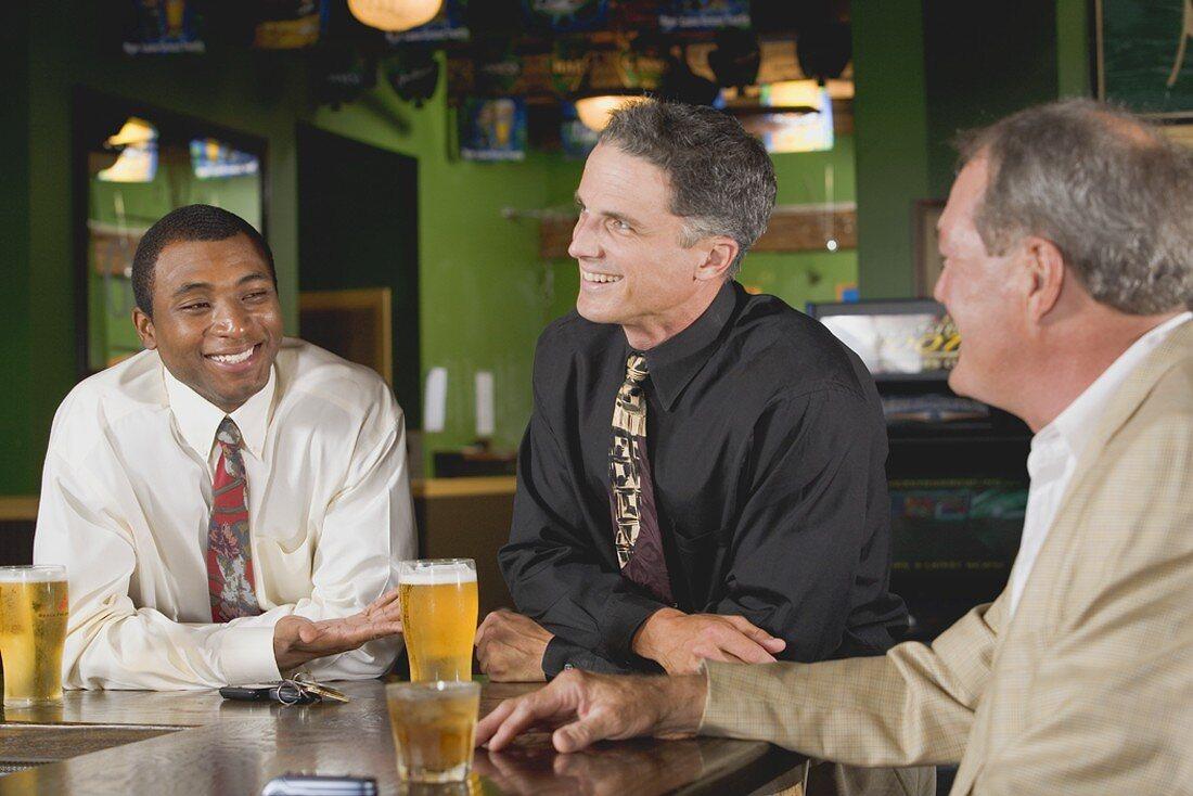 Drei Männer an der Bar in einem Pub