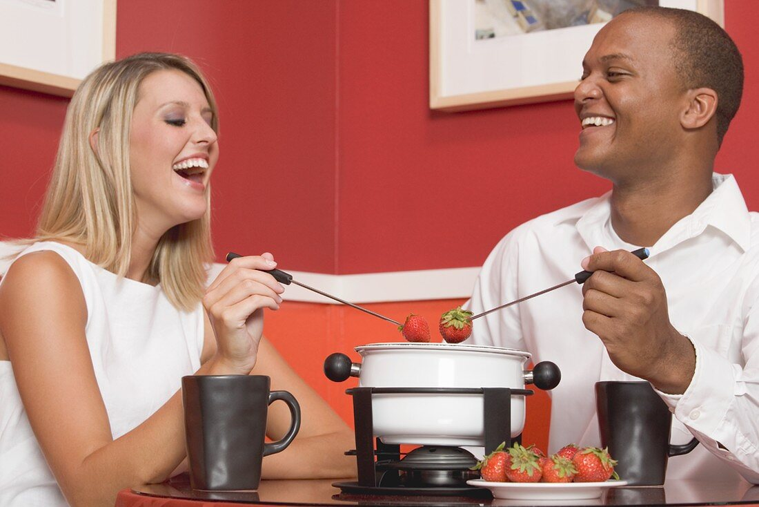 Young woman & man eating chocolate fondue with strawberries