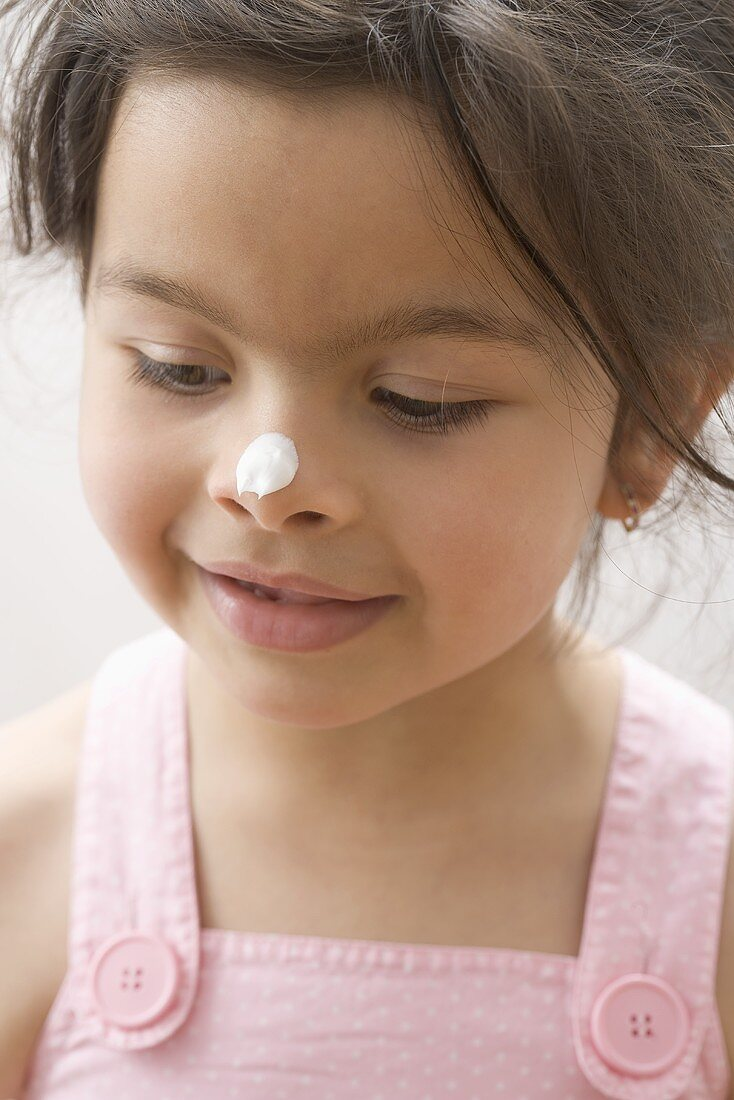 Girl with a blob of cream on her nose