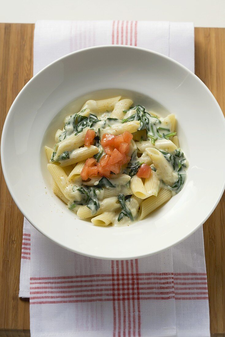 Penne rigate with spinach and cream sauce and diced tomato