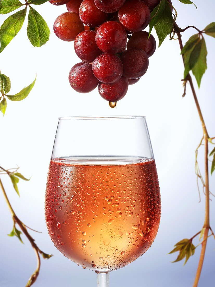 Rosé wine dripping from grapes into wine glass
