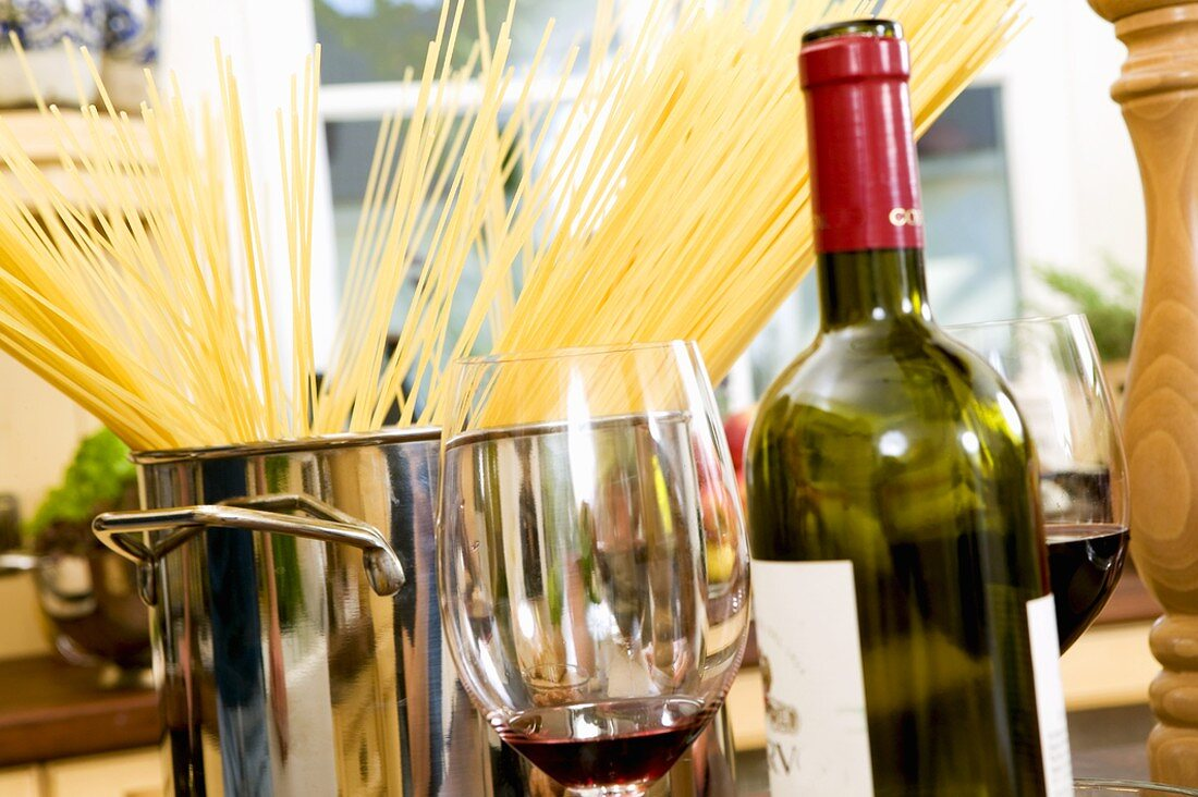 Spaghetti in pan, bottle and glasses of red wine in front